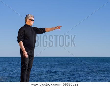 Handsome Man Standing Pointing At The Seaside Copy-space