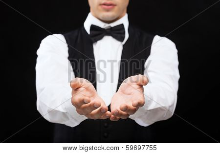 magic, performance, circus, casino and show concept - casino dealer holding something on palms of his hands