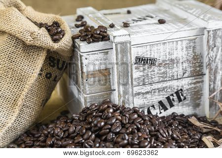 Wooden Box From The Supply Of Coffee Next To Burlap Bag Filled With Coffee Beans