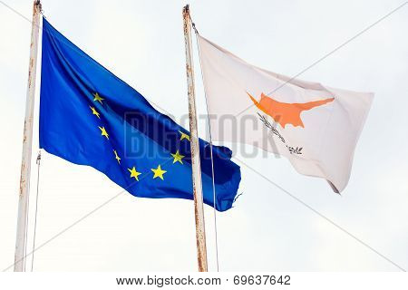 Torn EU flag, along with waving Cyprus flag, both on rusty flagpoles