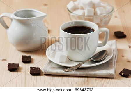 White Cup Of Coffee With Chocolate And Sugar In Wooden Table