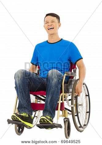 Cheerful Young Man Sitting On A Wheelchair In Studio