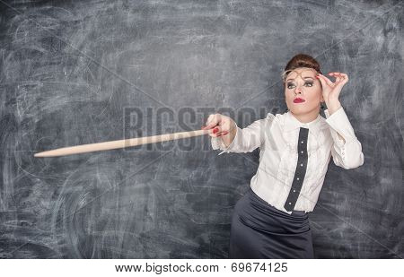 Strict Teacher Showing On Something By Wooden Pointer