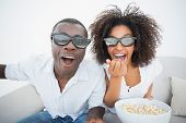 Couple sitting on couch together watching 3d movie at home in the living room poster
