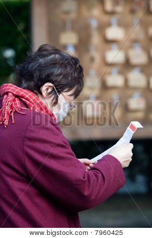 Japanese woman reading her omikuji fortune
