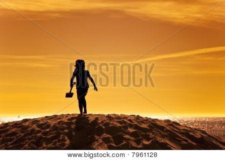 Silhouette Of Little Girl On Beach In Sunset