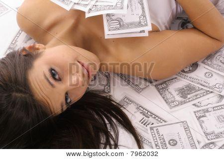 美丽的女人躺在钱