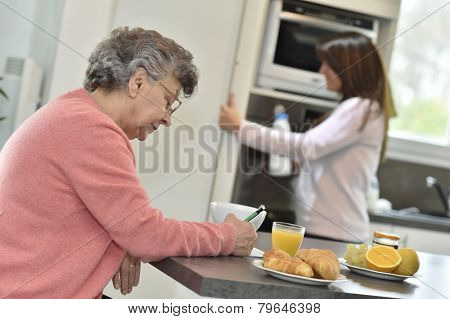 Elderly woman doing crossword while homecarer helps at home
