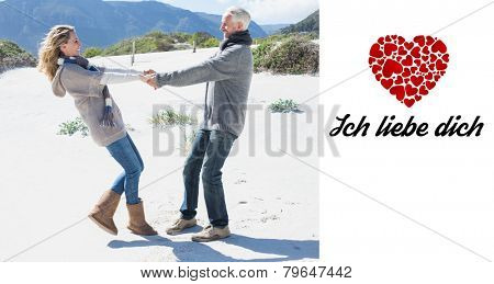 Smiling couple spinning on the beach in warm clothing against ich liebe dich