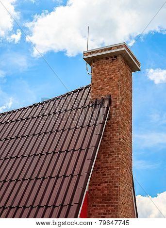Chimney On The Tile Roof Against Sky