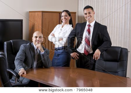 Three Hispanic Office Workers In Boardroom