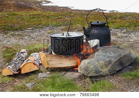 Outdoor cooking on campfire.