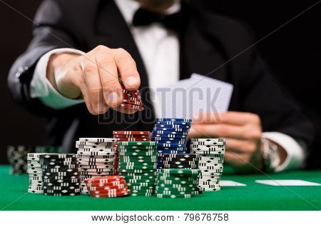 casino, gambling, poker, people and entertainment concept - close up of poker player with playing cards and chips at green casino table poster