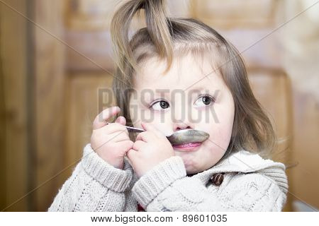 Little Girl With A Spoon In The Mouth