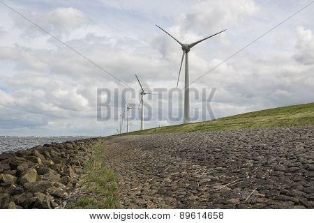 Modern windmills nearby the dike in the Netherlands
