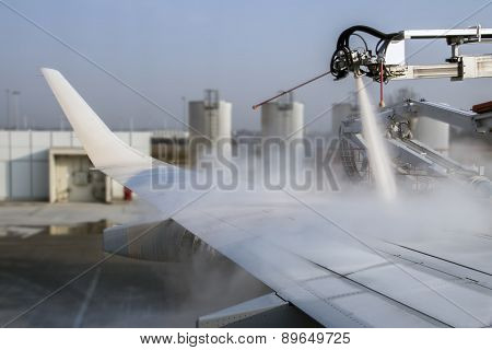 Munich, Germany - March 21, 2015: De-icing procedure of an airplane before take-off