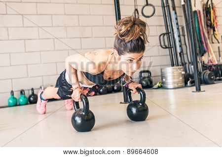 Woman Making Push Ups On The Kettle Bells