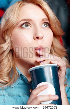 Young woman enthusiastically drinking soda in cinema