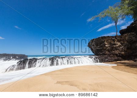 Wave splashing over volcanic rock ledge on a beautiful-serene beach under a blue sunny sky tree