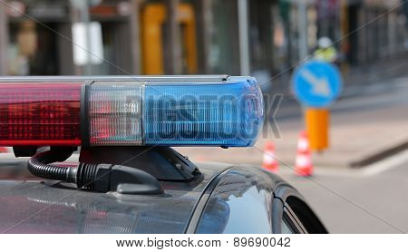 Blue and red flashing sirens of police car during the roadblock in the city poster
