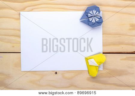 two origami hearts and white paper sheet for love letter.