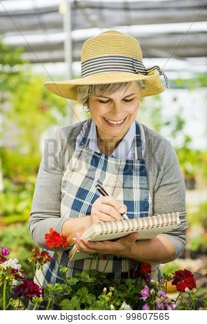 Mature woman in a greenhouse taking notes on a notebook