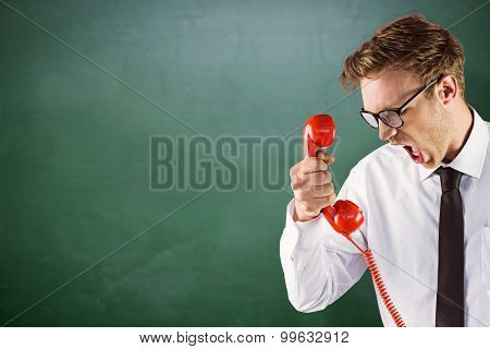 Angry geeky businessman holding telephone against green chalkboard