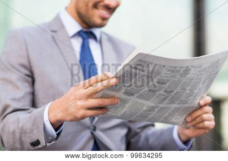 business, press, news and people and concept - close up of young smiling businessman reading newspaper over office building