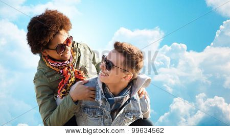 friendship, leisure, freedom and people concept - happy international teenage couple in shades having fun over blue sky and clouds background poster