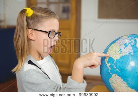 Astonished pupil pointing on globe in a classroom in school