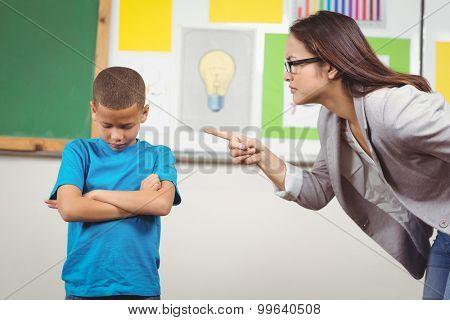 Pretty teacher reprimanding a pupil in a classroom poster