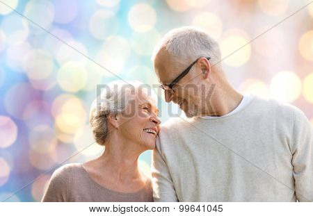family, age, love, relations and people concept - happy senior couple over holidays lights background