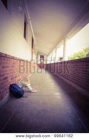 Sad pupil sitting alone on ground at corridor poster