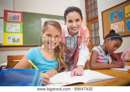 Pupil and teacher smiling at camera during class at the elementary school