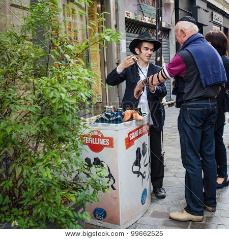 Young Orthodox Jewish man discusses the Tefilline with a passer-by