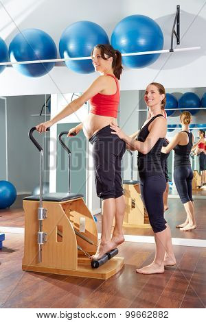 pregnant woman pilates tendon stretch exercise in wunda chair at gym with personal trainer poster