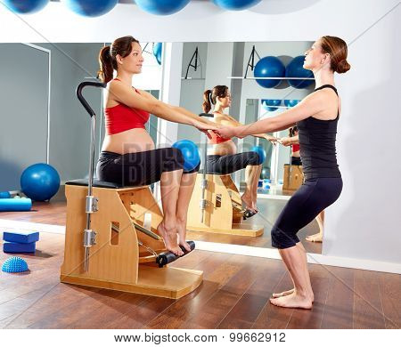 pregnant woman pilates leg pumps exercise on wunda chair with personal trainer