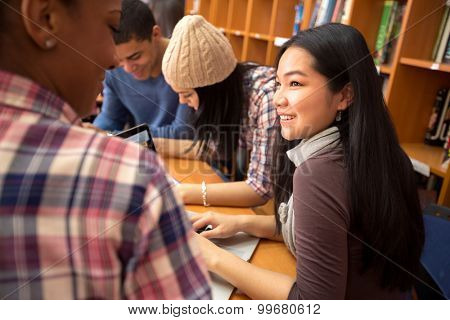 Studding friends socializing and studying together in library