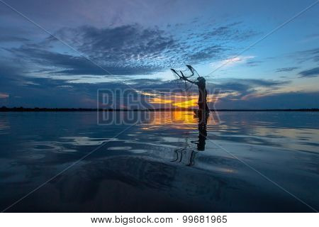 Silhouette fisherman with net at the lake in Thailand