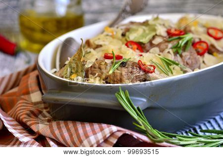 Pork ribs stewed with sour cabbage on a wooden table. poster
