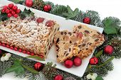 Stollen christmas cake on a plate with red bauble decorations, holly, mistletoe and winter greenery over white background. poster