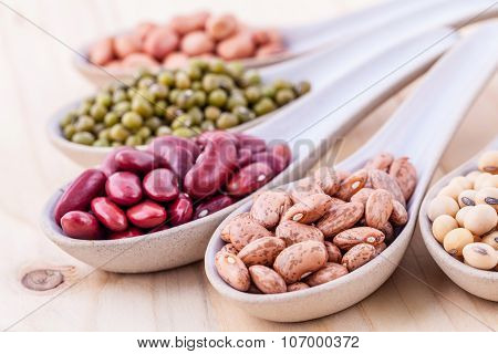 Assortment Of Beans And Lentils In Wooden Spoon On Wooden Background. Mung Bean, Groundnut, Soybean,