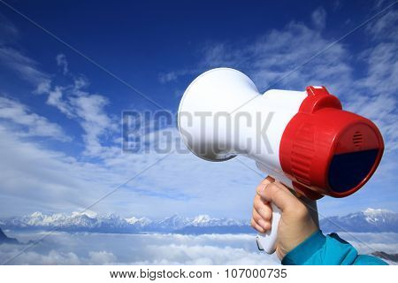 hand hold loudspeaker to blue sky on mountain peak