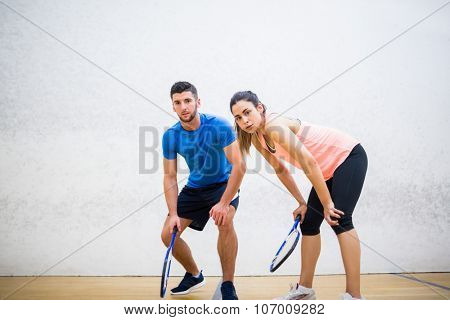 Couple tired after a squash game in the squash court