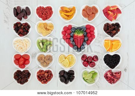 Assortment of healthy fruit in heart shaped dishes with fruits high in antioxidants, vitamin c and dietary fiber over distressed wooden background.