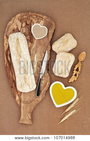 Italian ciabatta bread loaf on an olive wood board with yeas. knife and wheat sheath, with rolls and oil in a heart shaped bowl.