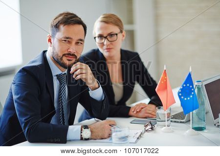 Businessman looking with suspicion during registration of foreign partners before conference
