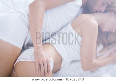 Married Couple Embracing In Bed