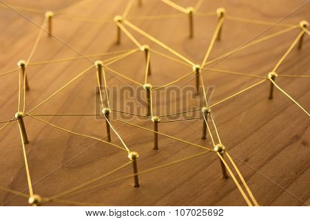 Linking entities. Network, networking, social media, internet communication abstract. Web of gold wires on rustic wood.