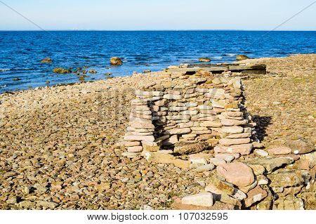 A hunting shelter made of flat limestone stacked on top of each other. These are used when hunting waterfowl. They also give some protection against the wind. poster